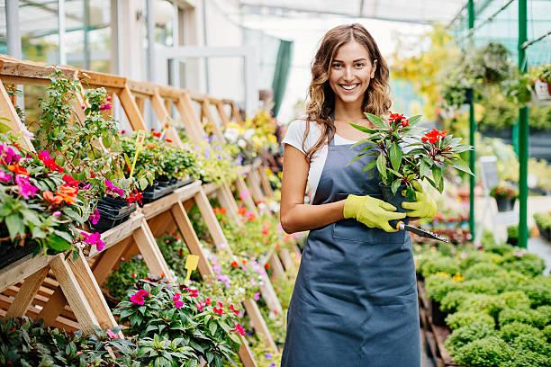 lächelnder junge gardener - gartenbau betrieb stock-fotos und bilder
