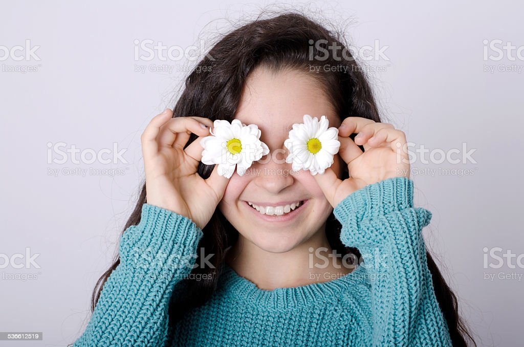 Smiling Young Girl Covering her eyes with Flowers stock photo