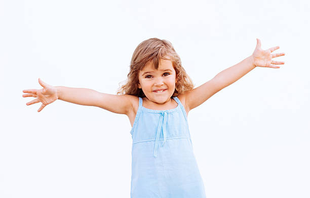 smiling young girl in a blue dress with arms outstretched - arms outstretched stock photos and pictures
