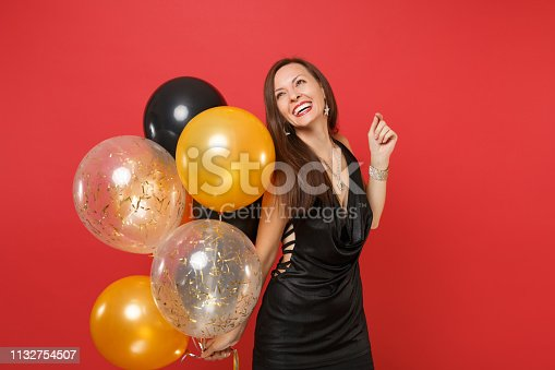 istock Smiling young girl in little black dress celebrating looking up holding air balloons isolated on bright red background. International Women's Day, Happy New Year birthday mockup holiday party concept. 1132754507