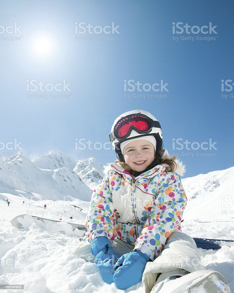 Smiling young girl in ski gear in a snowy scene royalty-free stock photo