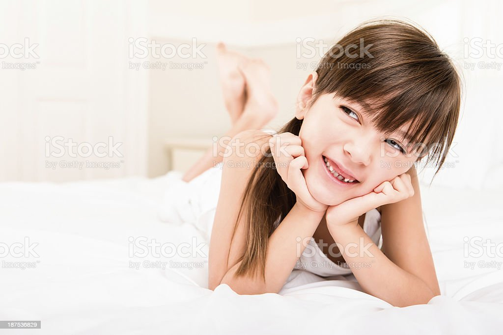 Smiling young girl laying in bed royalty-free stock photo