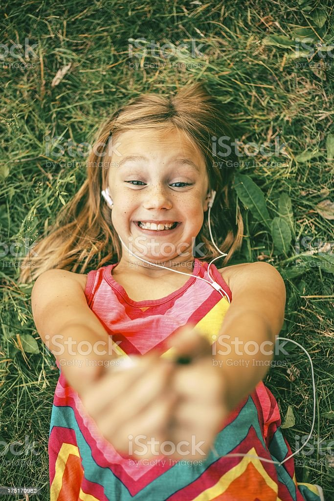smiling young girl laying in grass with MP3 player royalty-free stock photo