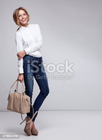 Attractive blonde cheerful woman posing with handbag. Studio shot.