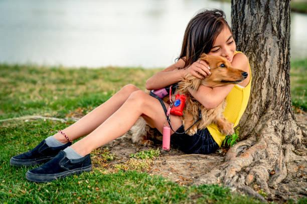 Smiling young girl resting by a tree holding embracing and petting picture id1221667016?b=1&k=6&m=1221667016&s=612x612&w=0&h=8gp5bxr86icpmqy7jiqk1 sinpbeuhzwyjsj5uao7v4=