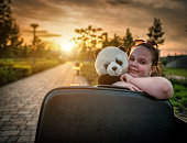 Smiling young girl sitting on a bench and hugging her panda