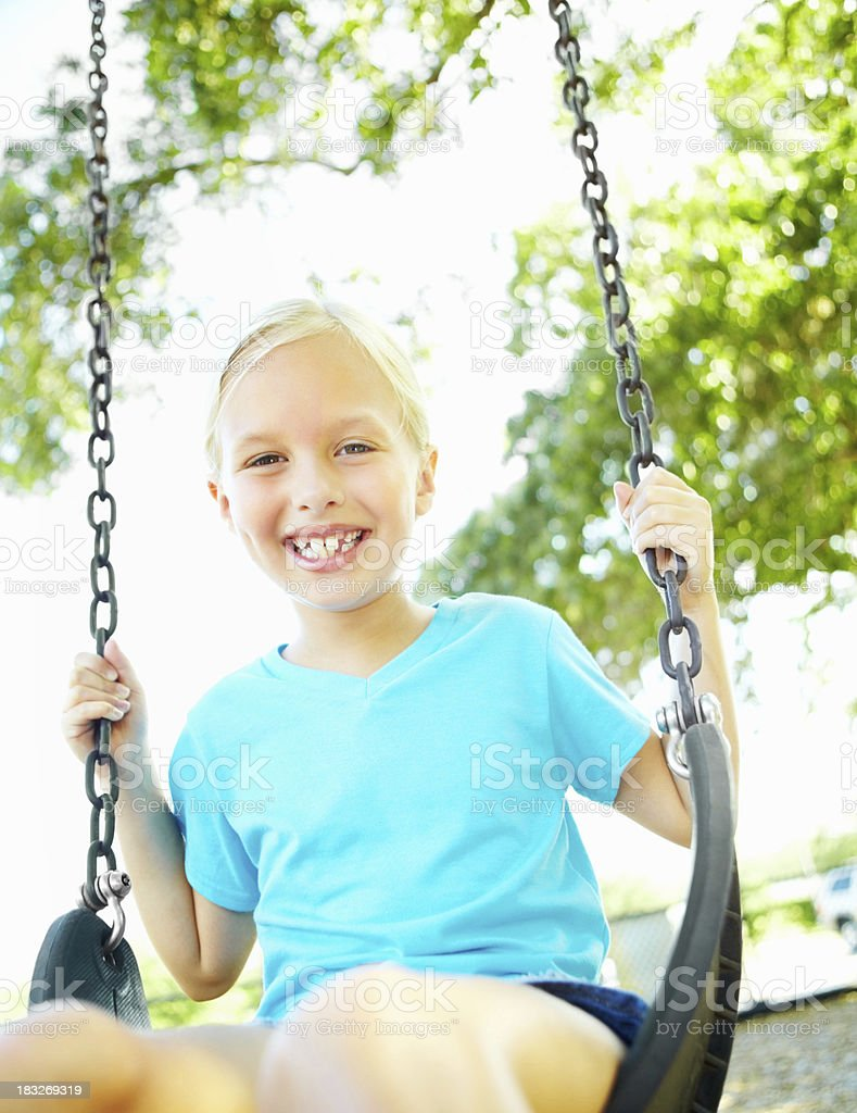 Smiling young girl sitting on swing at park royalty-free stock photo