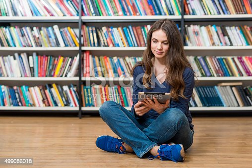 istock smiling young girl sitting on the floor in the library 499086018