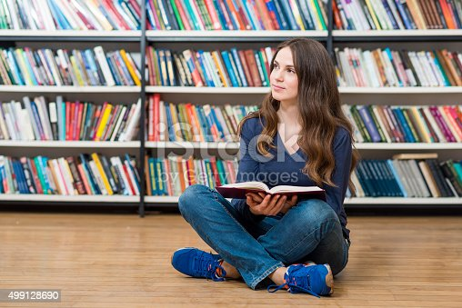 istock smiling young girl  sitting on the floor in the library 499128690