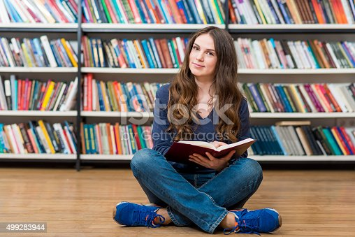 istock smiling young girl  sitting on the floor in the library 499283944