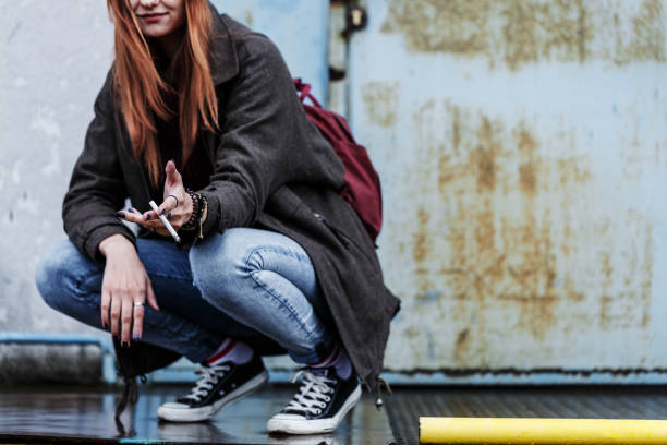 Smiling young girl smoking cigarette Close-up of smiling young girl smoking cigarette against concrete wall absentee stock pictures, royalty-free photos & images