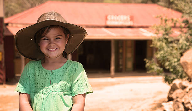 smiling young girl wearing a hat in australian outback - bush stockfoto's en -beelden