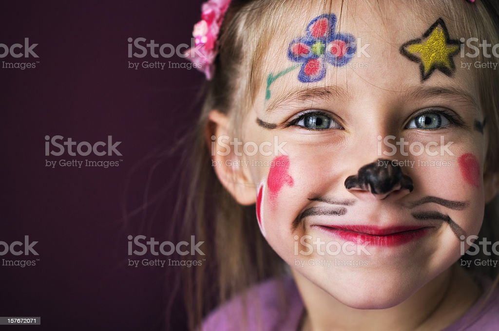 Smiling young girl with a painted face stock photo