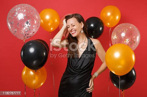 istock Smiling young girl with closed eyes in black dress celebrating, putting hand on head on bright red background air balloons. St. Valentine's Day, Happy New Year, birthday mockup holiday party concept. 1132757777