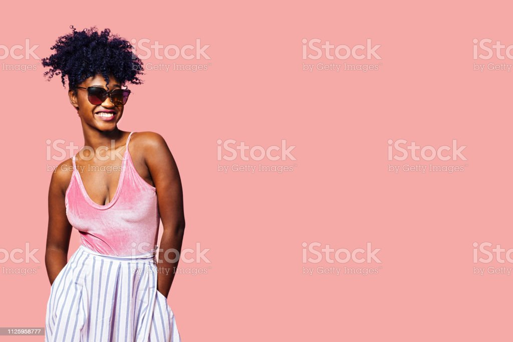Smiling young girl with sunglasses and pink top Smiling young girl with sunglasses and pink top, isolated on pink studio background Adult Stock Photo