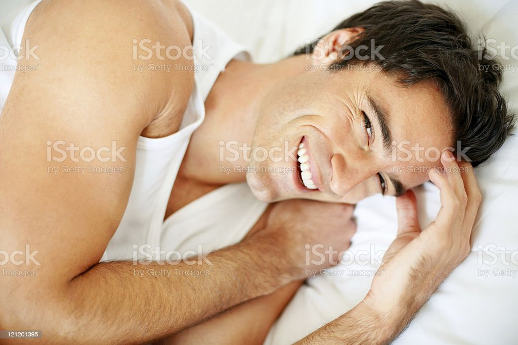 Smiling young guy lying in bed royalty-free stock photo