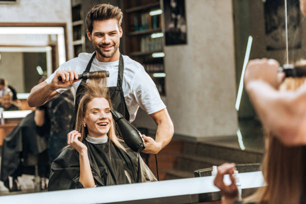 smiling young hairstylist combing and drying hair to happy young woman in beauty salon - hairdresser стоковые фото и изображения