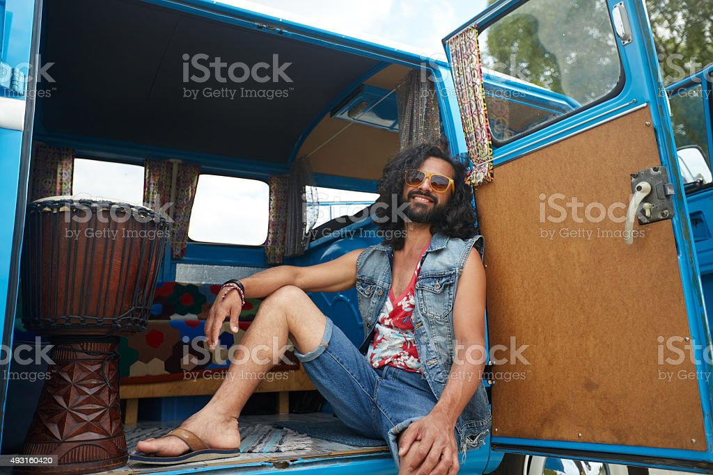 smiling young hippie man in minivan car stock photo