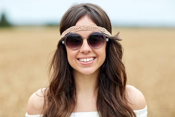 lächelnde junge hippie frau in sonnenbrille im freien - hippie stirnbänder stock-fotos und bilder
