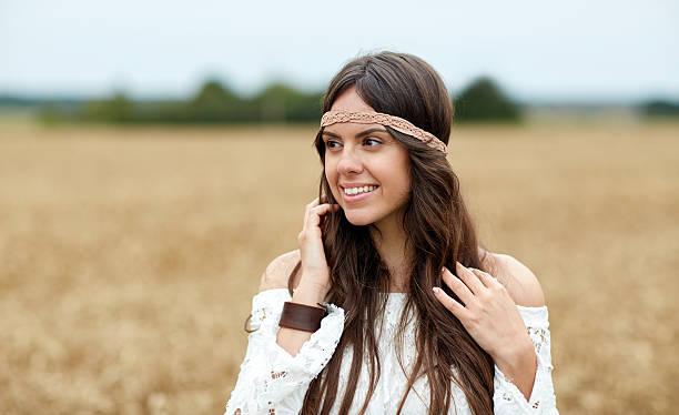 lächelnde junge hippie frau auf zerealien field - hippie stirnbänder stock-fotos und bilder