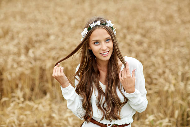 smiling young hippie woman on cereal field nature, summer, youth culture and people concept - smiling young hippie woman wearing flower wreath on cereal field romani people stock pictures, royalty-free photos & images