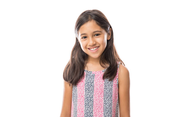 Smiling young hispanic girl posing and looking at the camera over white background Portrait of young beautiful little girl with t-shirt smiling to camera over white background 8 9 years stock pictures, royalty-free photos & images