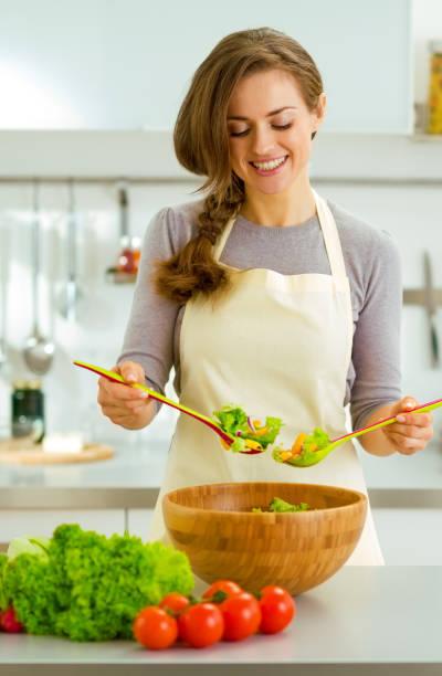 Lächelnde junge Hausfrau, frischen Salat mischen – Foto