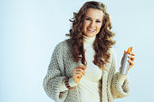 smiling young housewife with long wavy hair in neck sweater and cardigan with hair product isolated on winter light blue background.