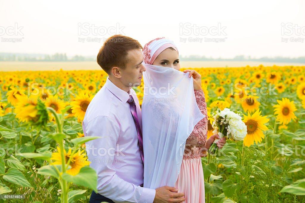 Smiling young islamic couple portrait on sunflowers field photo libre de droits
