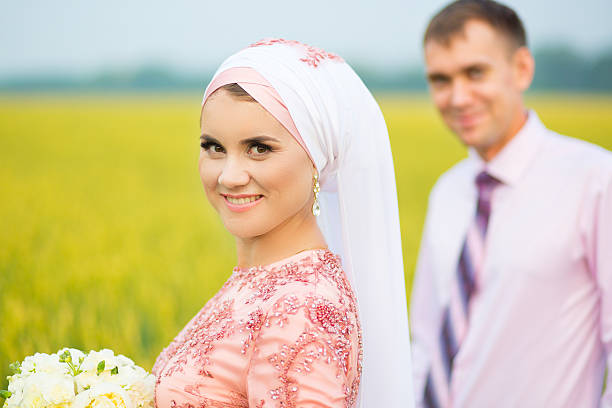 smiling young islamic couple portrait on sunflowers field - mariage musulman photos et images de collection