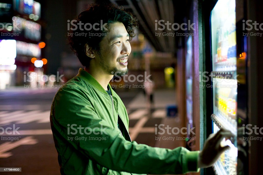 Smiling Young Japanese Man Using Vending Mashine in Tokyo. stock photo