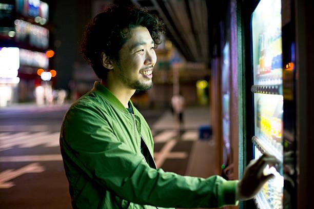 Lächelnder, junger, japanische Mann mit Verkaufsautomaten Mashine in Tokio. – Foto