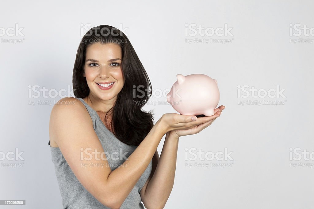 Smiling young lady holding piggy bank royalty-free stock photo