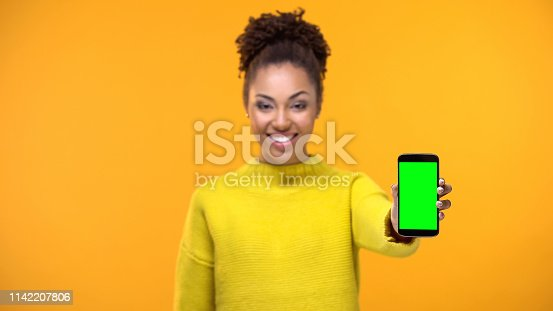 istock Smiling young lady in yellow sweater showing smartphone with green screen, app 1142207806