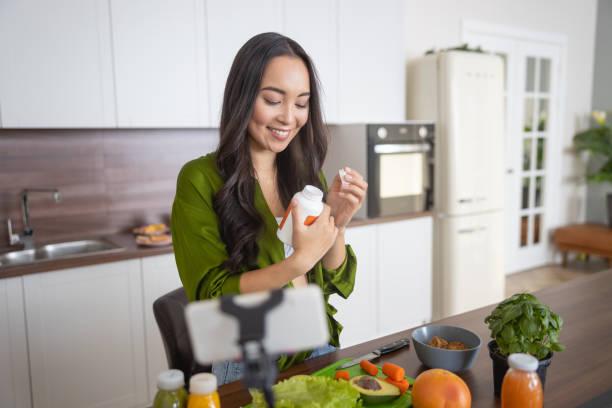 lächelnde junge dame, die ihre vitamine anschaut - nahrungsergänzungsmittel stock-fotos und bilder