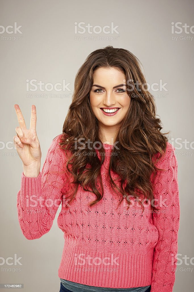 Smiling young lady showing victory sign stock photo