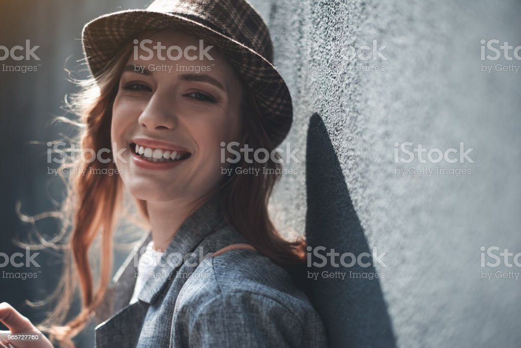 Smiling young lady standing near wall - Royalty-free Admiration Stock Photo