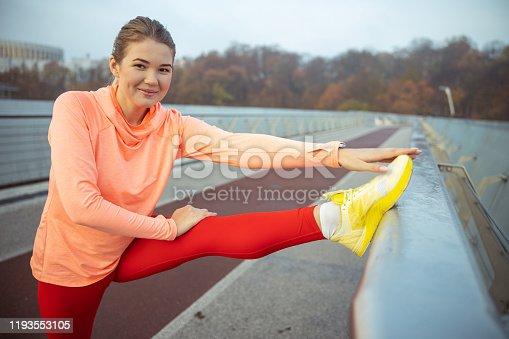 Joyful pretty girl doing morning exercise on the bridge stock photo