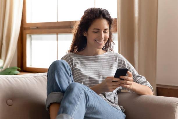 Lächelnde junge Dame mit mobilen Anwendungen zu Hause. – Foto