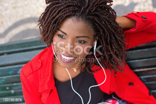Smiling young lady with earphones relaxing on street. Beautiful African American woman with dreadlocks listening to music. Leisure concept
