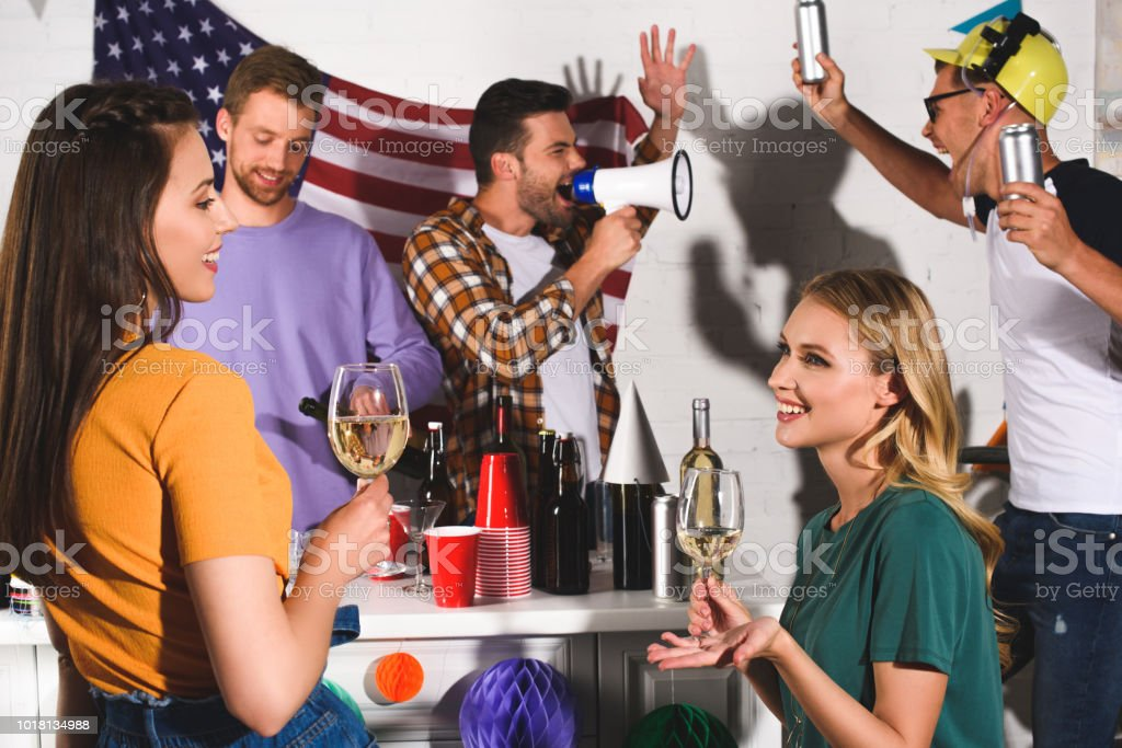 smiling young male and female friends drinking wine and beer while partying together stock photo
