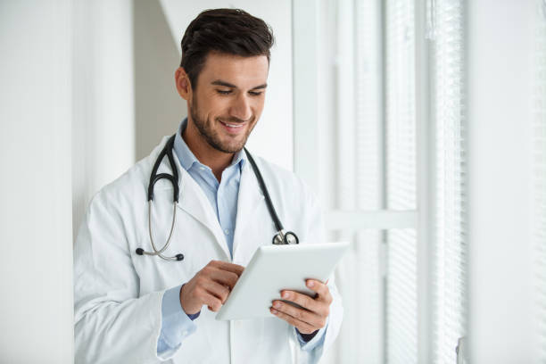 Smiling young male doctor using digital tablet at work stock photo