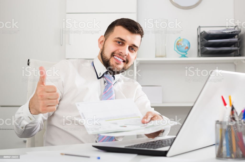 Smiling young male happy to book hotel online stock photo