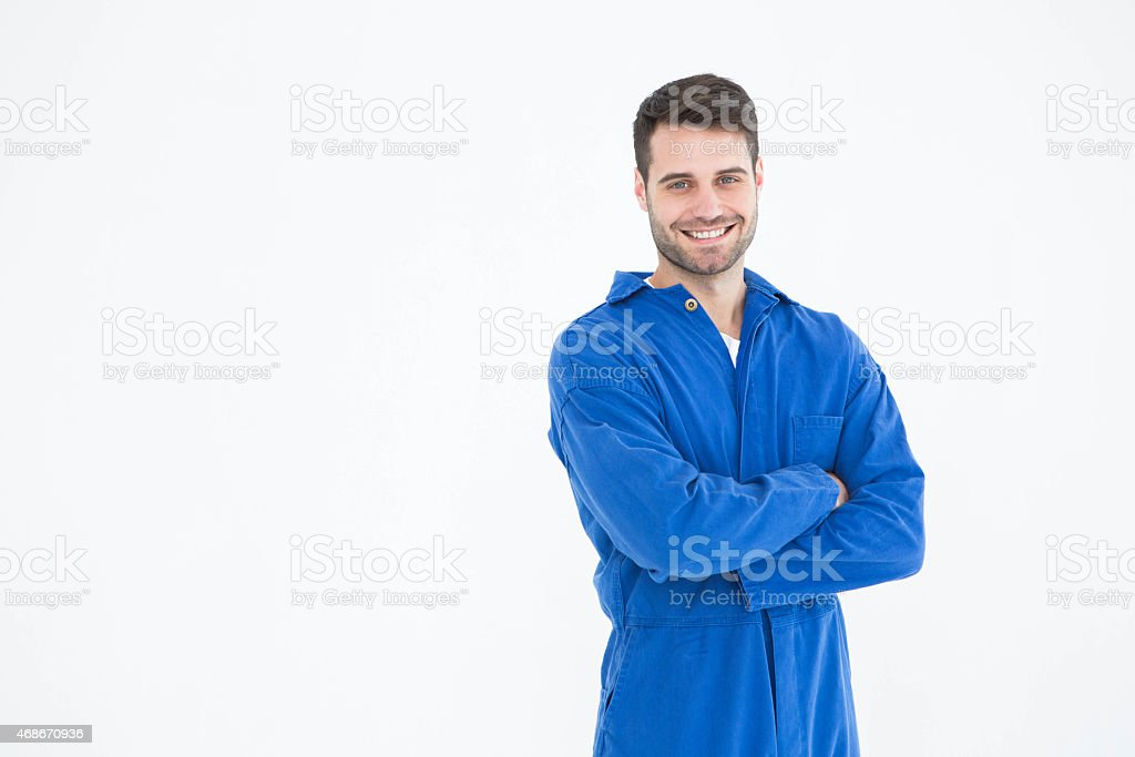 Smiling young male machanic standing arms crossed stock photo