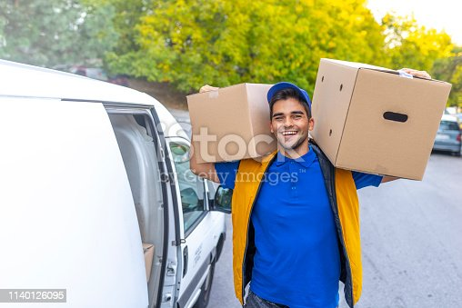 635967404 istock photo Smiling young male postal delivery courier man in front of cargo van delivering package 1140126095