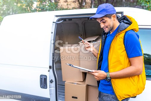 635967404 istock photo Smiling young male postal delivery courier man in front of cargo van delivering package. 1140127223