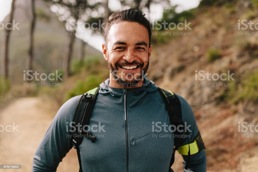Smiling young male runner on country road stock photo