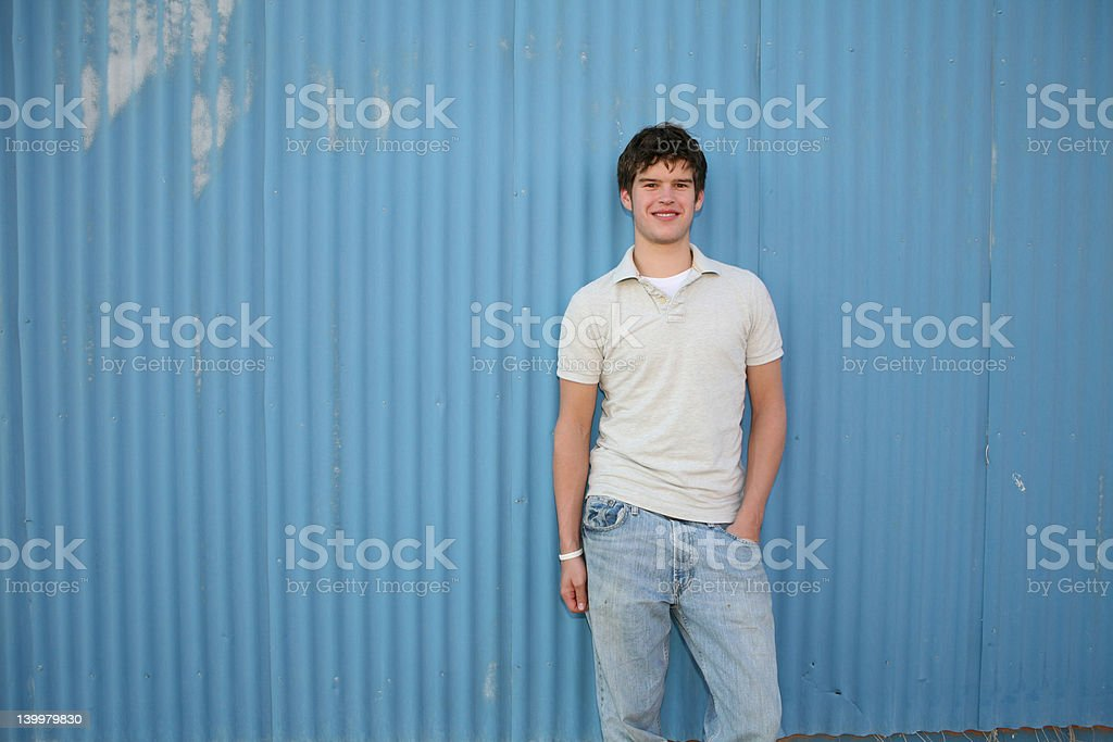 Smiling young man against blue wall royalty-free stock photo