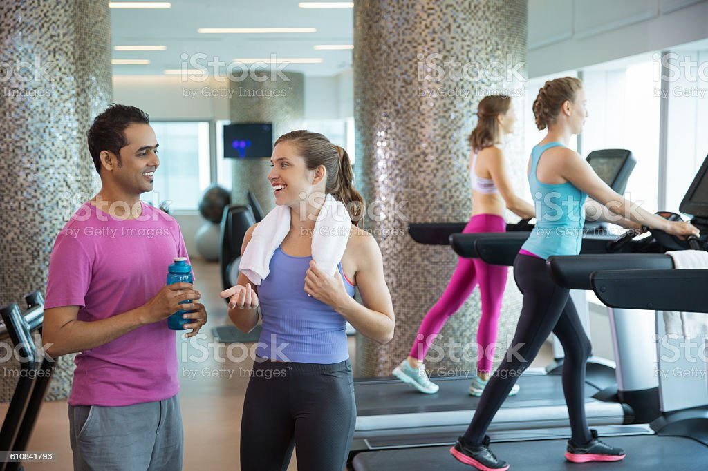 Smiling young man and women chatting in gym stock photo