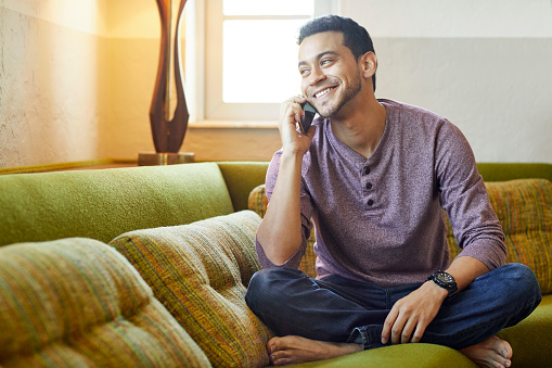 Smiling young man answering smart phone on couch. Happy confident male is looking away at home. He is enjoying conversation in living room.